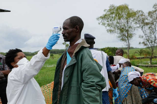 A medical staff takes temperature at Gatumba, Burundi, near boat with DR Congo (Photo by ONESPHORE NIBIGIRA / AFP)