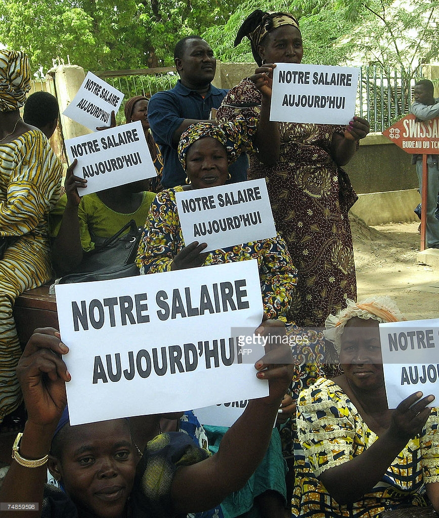 """Chadian workers with placards in French that read """"our salaries now"""""""