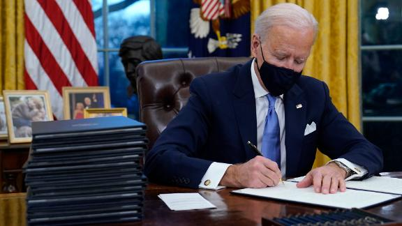 President Joe Biden signs executive orders, one of which rescinded the Trump travel ban - AP Photo/Evan Vucci