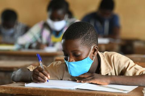 Masked Ghanaian schoolboy taking notes in classroom