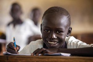 South Sudanese schoolboy looks up from his classroom desk