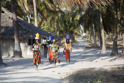 Women walk the sandy paths of Matemo Island