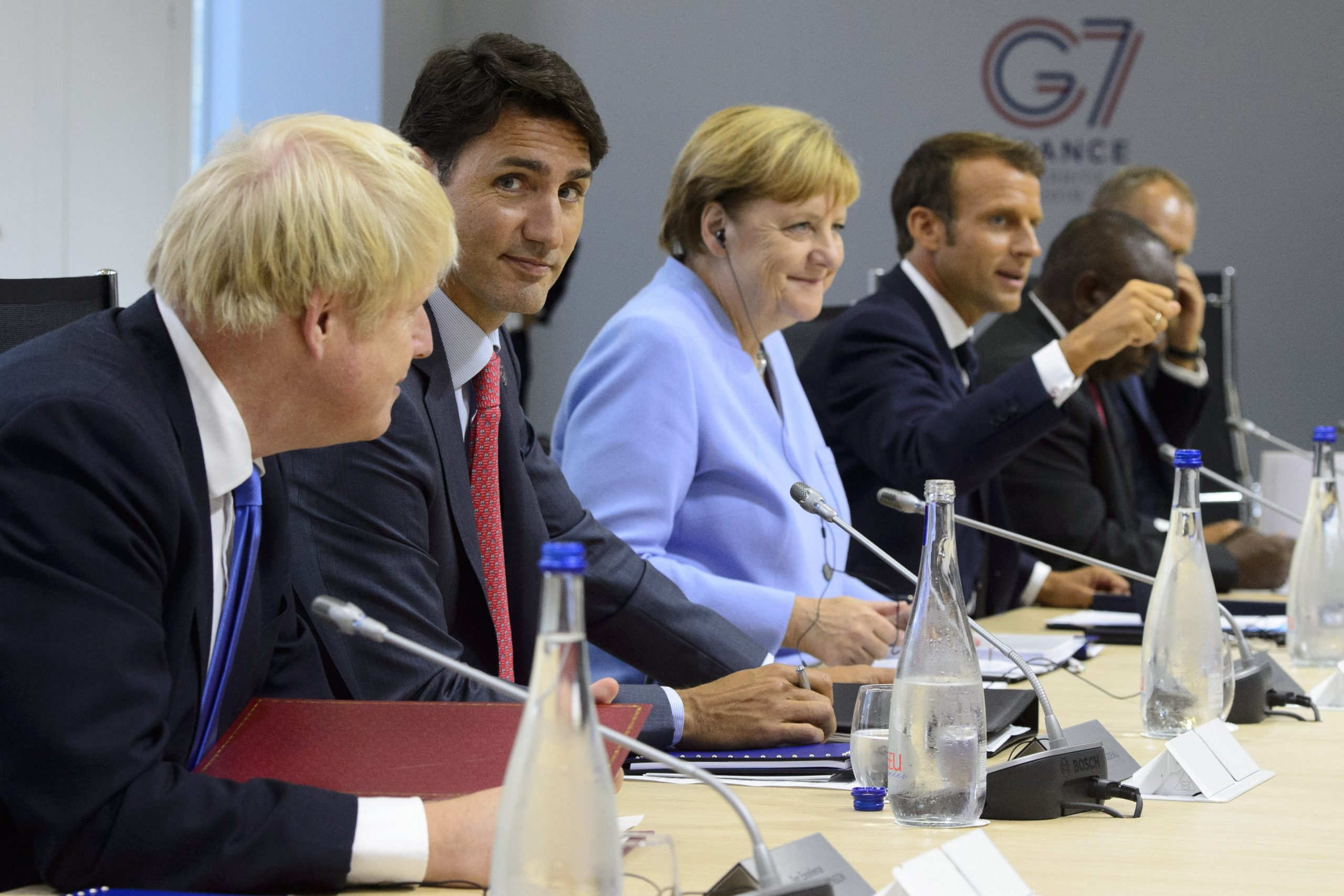 Justin Trudeau, second from left, sits between Boris Johnson (L), Angela Merkel at the G7 Summit in Biarritz, France, 26 Aug. 2019 - Photo Sean Kilpatrick/The Canadian Press via AP