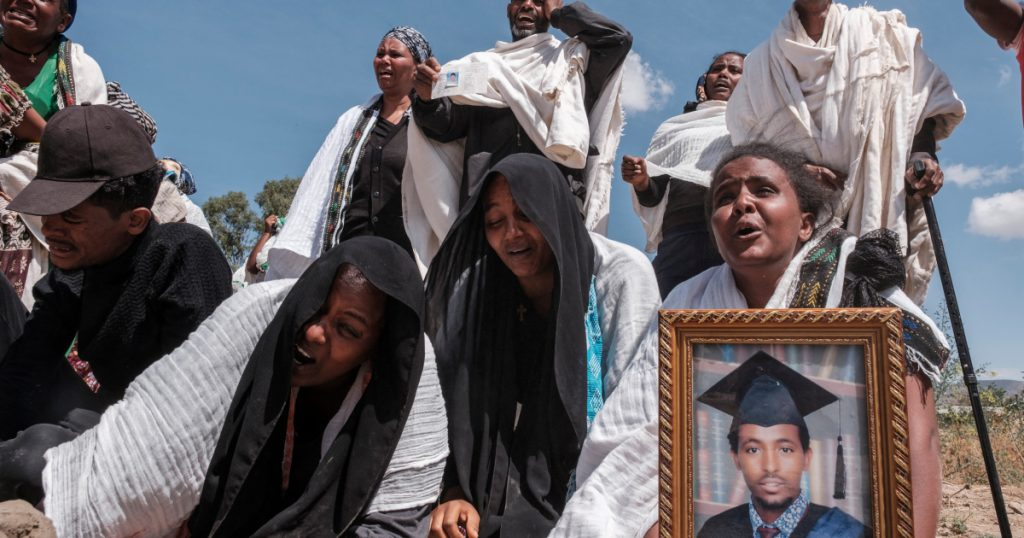 People mourn next to a mass grave holding the mortal remains of 81 victims in the city of Wukro, Tigray, on February 28, 2021 - Photo Eduardo Soteras, AFP