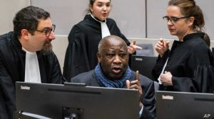 Laurent Gbagbo talks to his members of his legal team at the ICC - Photo Jerry Lampen, AP