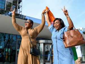 Two Ivorian Ladies Flash Victory Signs and Wave the Ivorian Flag Outside the Court - Photo Good Word News