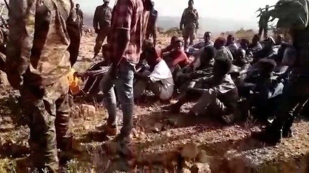 Unarmed Civilians Seated on Bare Ground Just Before their Executions - Photo BBC