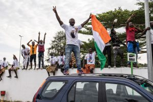 Supporters of Laurent Gbagbo Take to Car Roof-Tops to Catch a Glimpse as Gbagbo's Plane Arrives Abidjan on 17 June 2021 - Photo John Wessels, AFP